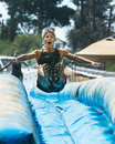 Woman jumping and getting ready to go down a slide boise idaho usa august unidentified jumps air time the dirty dash is k run Stock Photo