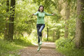Woman jumping on path smiling Royalty Free Stock Photo