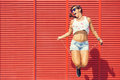 Woman jumping rope on red background Stock Photos