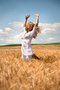 Woman jumping in wheat field blond white dress or leaping a of Stock Photography
