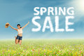 Woman jumps with spring sale sign excited jumping on the park cloud design of Royalty Free Stock Image