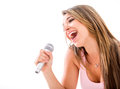 Woman karaoke singing with a microphone isolated over a white background Stock Images