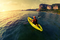 Woman with the kayak lady backpack paddling in calm bay at sunset Royalty Free Stock Photography