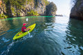 Woman with the kayak young lady paddling in calm bay limestone mountains Stock Photos