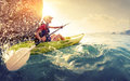 Woman with the kayak young lady paddling hard lots of splashes near cliff at sunny day Stock Photos
