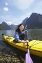 Woman kayaking in mountain lake young with mountains background Stock Photos