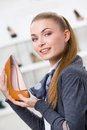 Woman keeping brown leather pump portrait of shoe in shopping center against the showcase with shoes Royalty Free Stock Images