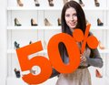 Woman keeps the model of sale on shoes standing at shopping center against showcase with pumps Royalty Free Stock Photos