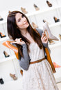 Woman keeps two shoes in the shopping mall and can t choose one for her Royalty Free Stock Photo