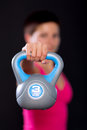 Woman with kettlebell attractive young exercising black background Stock Images