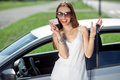 Woman with keys and lisence near her car young showing a key license in front of the girl pass successfully driving exam Stock Photo