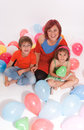 Woman and kids in a party aerial view of mom with boy girl playing with colourful balloons Royalty Free Stock Image