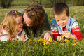 Woman and kids relaxing on the spring meadow Royalty Free Stock Images