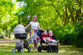 stock image of  Woman with kids in stroller in a park