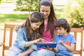 Woman with kids using digital tablet in park Stock Photo