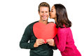 Woman kissing boyfriend with red heart shape on white background Stock Photo