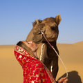 Woman kissing her camel in the desert. Stock Photography