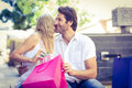 Woman kissing her smiling boyfriend after receiving a gift at shopping mall Royalty Free Stock Photo