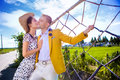 Woman kissing man while standing by fence at field against sky Royalty Free Stock Photo