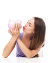 Woman kissing piggy bank casual young over white background Royalty Free Stock Photo