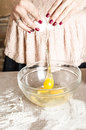 Woman in kitchen beating eggs backing and to white bowl with broken yolk hands Stock Images