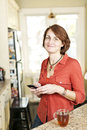Woman in kitchen with cell phone smiling mature using mobile at home Stock Photos