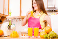 Woman in kitchen drinking fresh orange juice