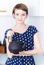 A woman in the kitchen holding a traditional style tea kettle Stock Photography