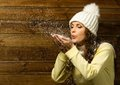 Woman in knit hat blowing snow beautiful from her hands Stock Images