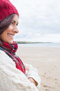 Woman in knitted hat and pullover smiling at beach close up side view of a young the Stock Image