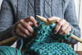 Woman knitting scarf with green wool Royalty Free Stock Photo