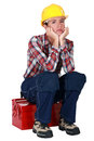 Woman laborer pouting whilst sat on a tool box Royalty Free Stock Photos