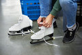 Woman laces figure skates in sports shop Royalty Free Stock Photo