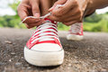 Woman lacing her shoes before jogging in park health Stock Image