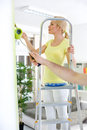 Woman on ladder painting young wall Royalty Free Stock Image