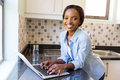 Woman laptop computer beautiful young black using on kitchen counter Royalty Free Stock Image