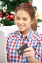 Woman with laptop computer and credit card happy over christmas tree Stock Image