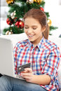 Woman with laptop computer and credit card happy over christmas tree Stock Images