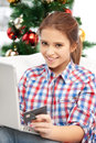 Woman with laptop computer and credit card happy over christmas tree Royalty Free Stock Images