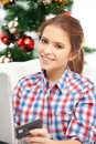 Woman with laptop computer and credit card happy over christmas tree Royalty Free Stock Photo