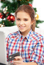 Woman with laptop computer and credit card happy over christmas tree Royalty Free Stock Image