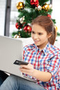 Woman with laptop computer and credit card happy over christmas tree Stock Photography
