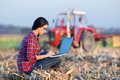Woman with laptop in corn field young sitting on the bale on the tractor background Royalty Free Stock Image