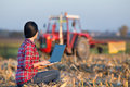 Woman with laptop in corn field young sitting on the bale on the tractor background Royalty Free Stock Images
