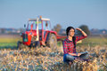 Woman with laptop in corn field young sitting on the ground of the tractor background Royalty Free Stock Images