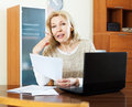Woman with laptop and documents at table serious mature home Royalty Free Stock Images