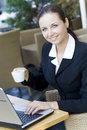 Woman with laptop drinking coffee Stock Photography