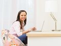 Woman with laptop in home interior cheerful young behind table Royalty Free Stock Image