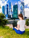 stock image of  woman with laptop notebook sitting on the grass. She is in blue jeans and a white t-shirt. Landscape with skyscrapers