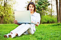 Woman with laptop in park pretty working on Royalty Free Stock Photo